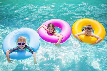 nadar: Grupo de niños lindos jugando en tubos inflables en una piscina en un día soleado