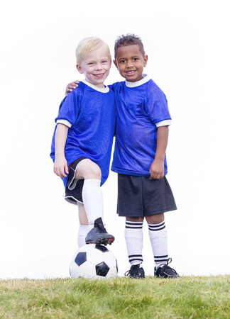 Two diverse young soccer players on white background. Full length view of two youth recreation league soccer players. Stock Photo