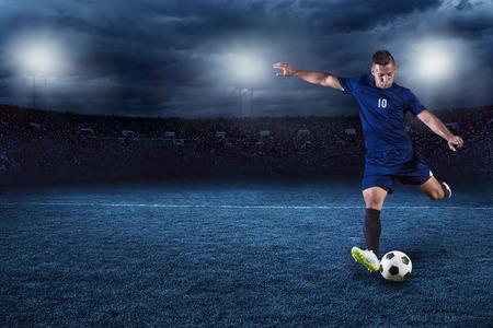 deportista: El f�tbol profesional o jugador de f�tbol durante el partido en el estadio iluminada llena en la noche Foto de archivo