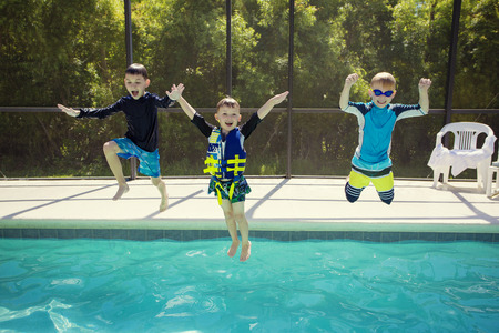 child swimsuit: Cute young boys jumping into a swimming pool while on a fun vacation Stock Photo
