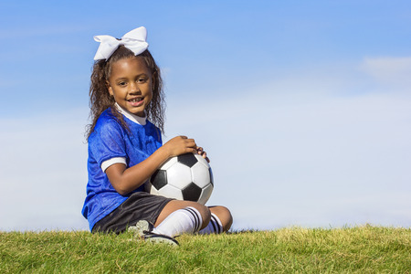soccer cleats: Cute, young african american girl soccer player holding a ball sitting on a grass field Stock Photo