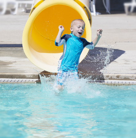 water splashing: Young boy sliding out of a yellow water slide Stock Photo