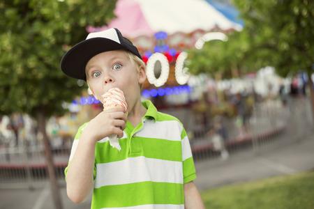 Ragazzo sveglio godere appieno un cono gelato durante un carnevale estivo o fiera. Sta facendo un'espressione eccitata Archivio Fotografico - 42202658