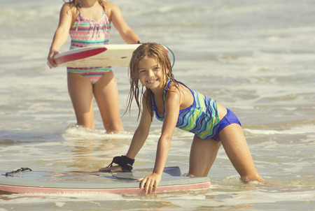 children at play: Cute Girl Playing in the Ocean on a boogie board