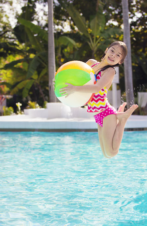 water splashing: Cute Girl playing and jumping in the swimming pool Stock Photo