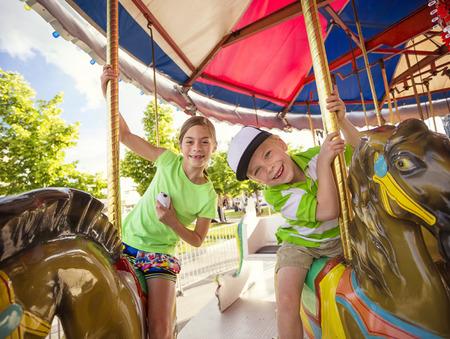 niños riendose: Niños lindos que se divierten montando en un carnaval colorido carrusel