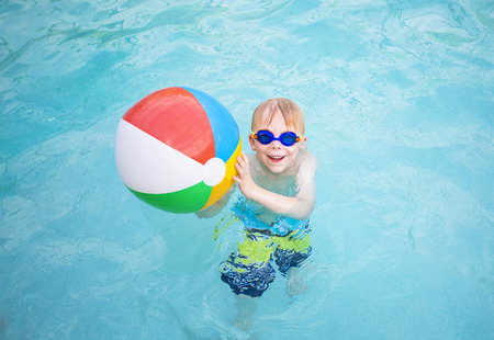 beach ball girl: Cute little girl playing with Beach ball in a swimming pool Stock Photo
