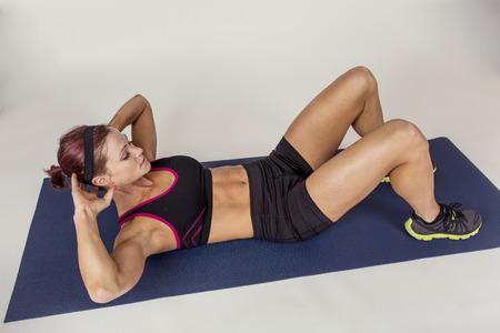 mujer cuerpo completo: Fuertes crujidos Mujer hermosa gimnasio haciendo abdominales