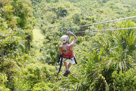 Woman going on a jungle zipline adventure. View from behind
