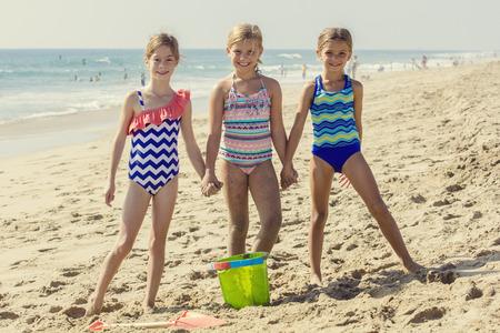 traje de bano: Retrato lindo de los tres mejores amigos jugando juntos en la playa Foto de archivo