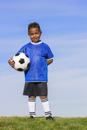 Young african american boy soccer player holding a ball standing on a grass field with a simple blue sky background.