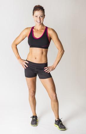 completos: Longitud total retrato de una bella mujer fuerte musculoso mirando a la cámara. Grave Constructor de sexo femenino cuerpo con las manos en las caderas