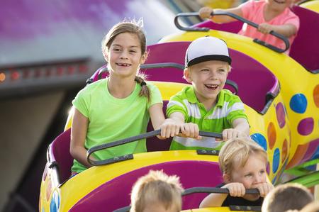 carnaval: Gar�on et fille sur un tour de montagnes russes palpitante � un parc d'attractions