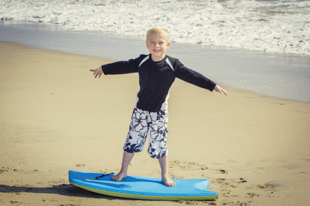 bogey: Happy Young boy having fun at the beach on vacation, trying to ride a bogey board