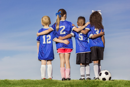 boys: Diverse group of boys and girls soccer players standing together with a ball against a simple blue sky background Stock Photo