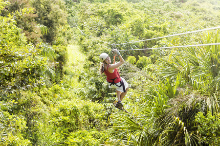 Woman going on a jungle zipline adventure. los of copy space