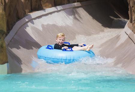 Happy little boy enjoying a wet ride down a water slide