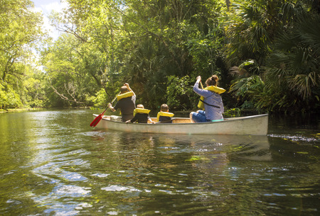 Family canoe ride down a beautiful tropical river. View from behind