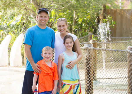 getting together: Beautiful young family enjoying a day at an outdoors amusement park