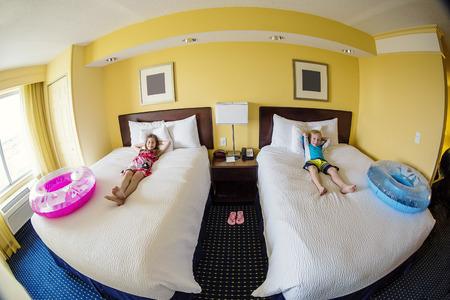 sandalias: Niños lindos que pone en una cama en una habitación de hotel, mientras que en la diversión de vacaciones familiares
