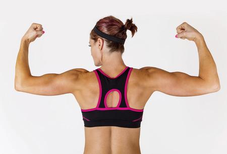 그녀의 팔뚝과 팔 근육 flexing 아름 다운 강한 근육 여자. 뒤에서보기 그녀를 다시 팔 찢어 표시합니다. 스톡 콘텐츠
