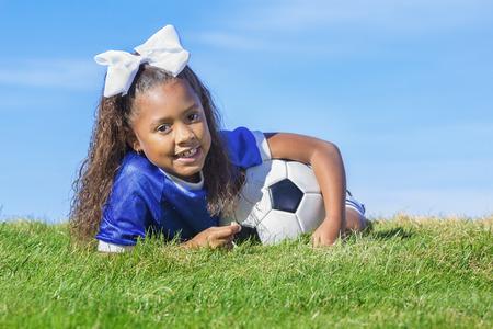 귀여운, 젊은 아프리카 계 미국인 여자 축구 선수 간단한 푸른 하늘 배경으로 잔디 필드에 누워 공을 들고. 복사 공간을위한 공간을 많이