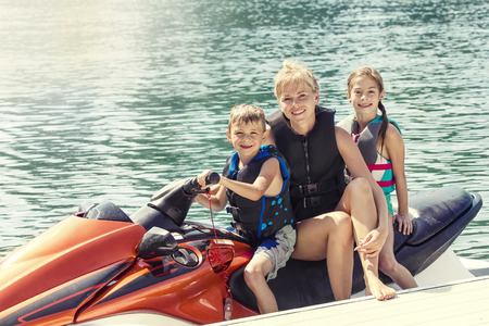Group of People enjoying a ride on a personal watercraft on a warm summer day on the lake Stock Photo