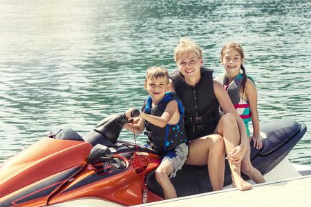 moto acuatica: Grupo de personas disfrutando de un paseo en una moto acuática en un cálido día de verano en el lago Foto de archivo