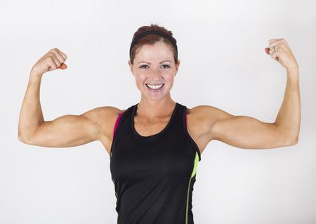 Een sterke gespierde vrouw buigen haar spieren. Mooie vrouw die op een witte achtergrond