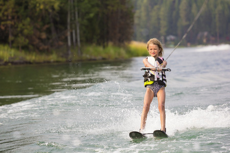 scenic background: Young Waterskier water skiing on a beautiful scenic lake. Lots of copy space with scenic background