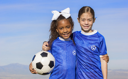 little league: Cute, young african american and hispanic female soccer players holding a ball with a simple blue sky background