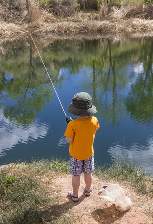 view from behind: Little boy fishing in a pond view from behind