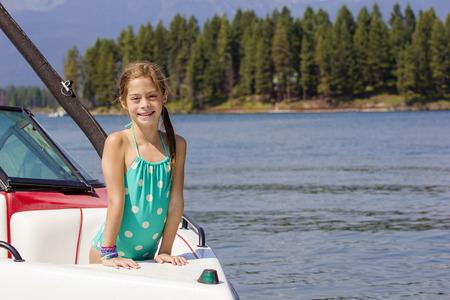 美しい湖でモーター ボートに乗る女の子。風光明媚な背景を持つコピー スペースがたくさん