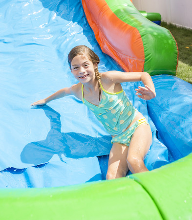 brincolin: Smiling little girl playing on an inflatable slide bounce house