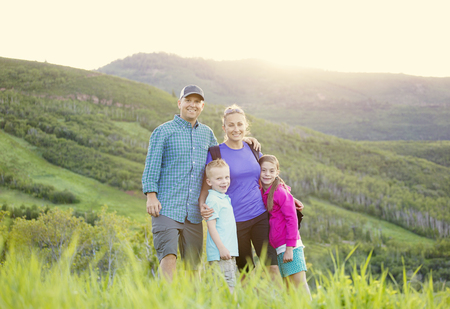 A beautiful young family hiking on a nice scenic evening in the rocky mountains of Utah in the United States of America Foto de archivo