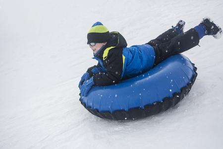 Child sledding down a hill on a snow tube on a snowy day outdoors
