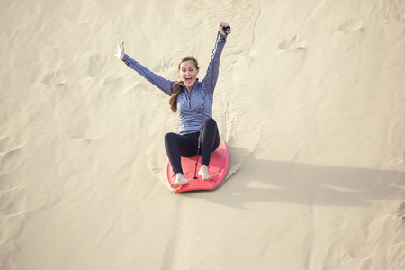 thrill: Outdoor Adventure seeker riding down a large sand dune with great speed and screaming with fun and excitement Stock Photo