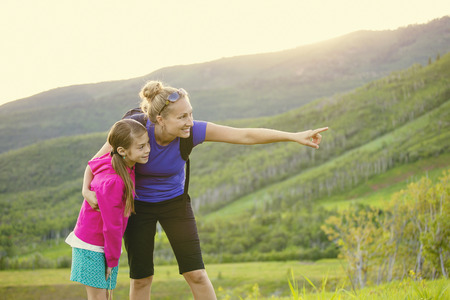 Family hiking in the mountains together. Young mother pointing out wildlife while she and her daughter take a hike together in the mountains on a beautiful summer evening Standard-Bild