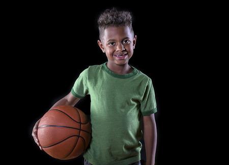 niños negros: Lindo chico joven afroamericano que sostiene una pelota de baloncesto y listo para jugar. Futuro retrato estrella del baloncesto Foto de archivo
