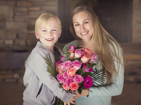 boy beautiful: Smiling Boy giving his mom a bouquet of beautiful pink roses Stock Photo