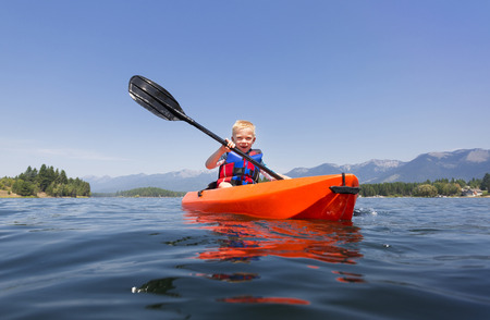 lifejacket: Young Boy paddling a kayak on a beautiful mountain lake. Low angle view of the natures beauty