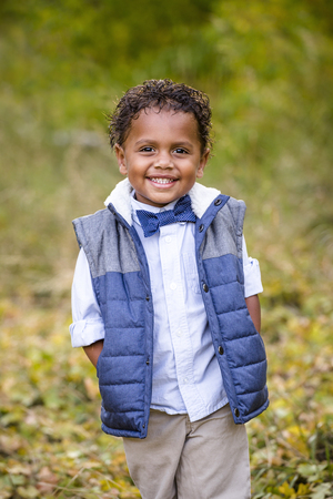 racially diverse: Cute outdoor portrait of a smiling African American boy