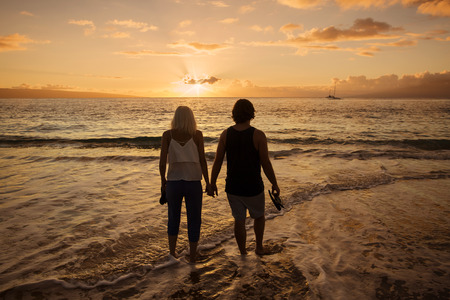 woman sunset: Couple in love walking along the beach barefoot together at sunset. Wide angle photo with lots of copy space