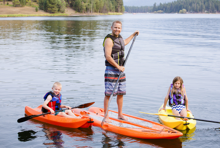Attractive family kayaking and paddle boarding together on a beautiful lake