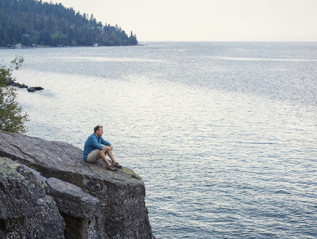 cliff edge: Middle aged man sitting on the edge of cliff overlooking a beautiful ocean bay thinking, meditating and praying