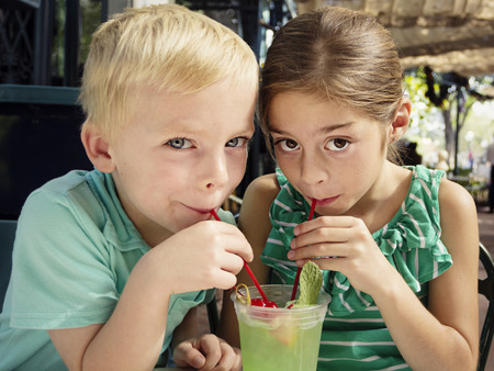 summertime: Cute kids sharing a mint julep drink at a cafe