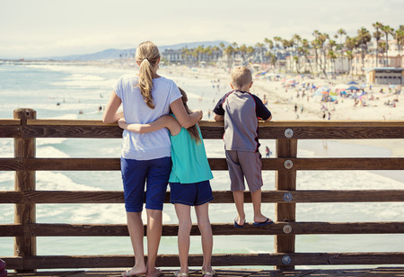 of boy and girl: Young family hanging out on an ocean pier on vacation in Southern California
