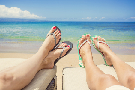 beach feet: Women Lounging and sunbathing on an idyllic beach Stock Photo