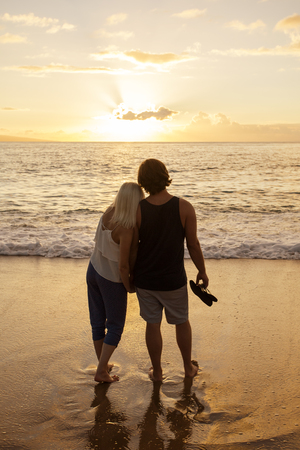honeymooners: Honeymoon Couple in love watching a sunset at the beach together