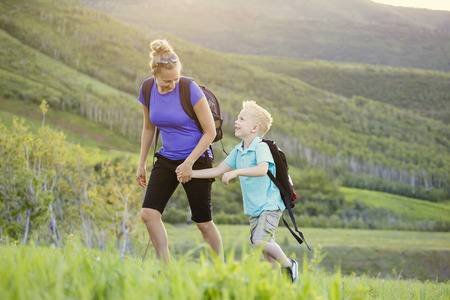 Family hiking in the mountains. A young mother and her son take a hike together in the mountains on a beautiful summer evening. Holding hands and enjoying their time together